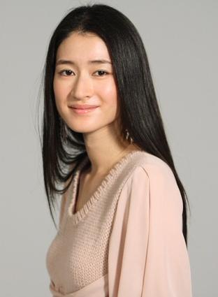 薄い桃色のニットを着て微笑む女優・小雪
